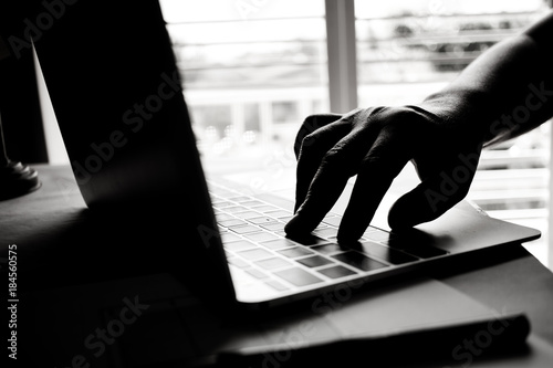Fototapety, obrazy: hands of anonymous hackers typing code on keyboard of laptop for remotely reach and receiving personal information online networking, Internet Crime Payment Security Concept, Silhouette black white
