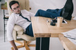 businessman sleeping in armchair with feet on table at office