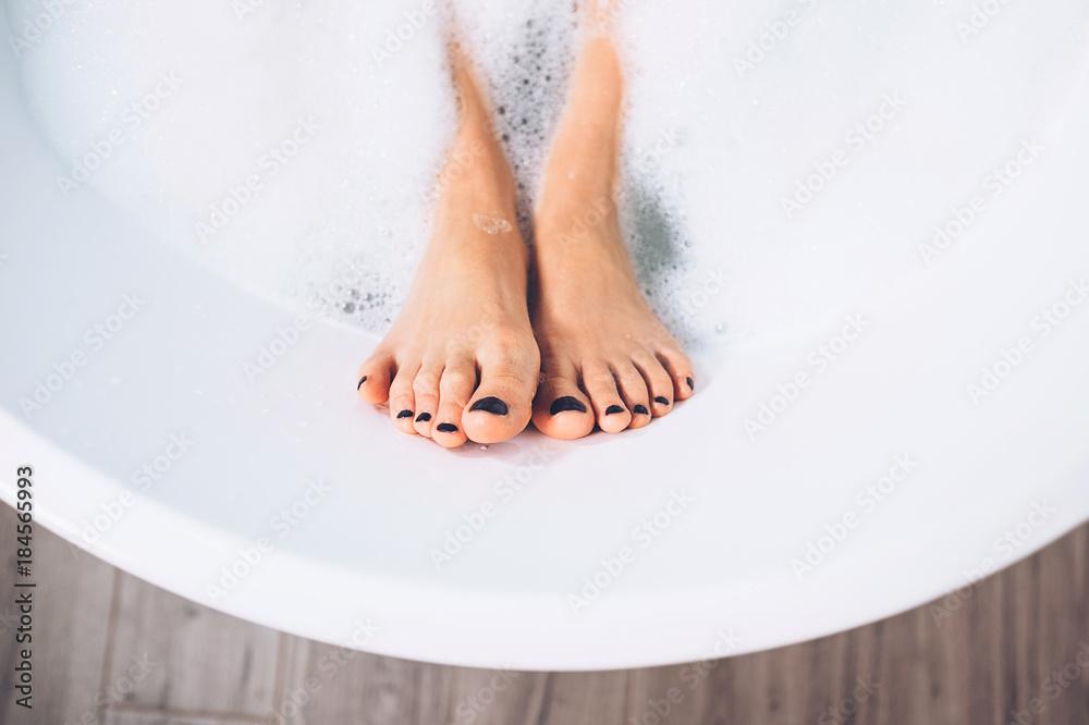 Fototapeta Well groomed woman's legs in bath foam close up image