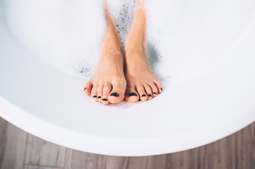 Well groomed woman's legs in bath foam close up image