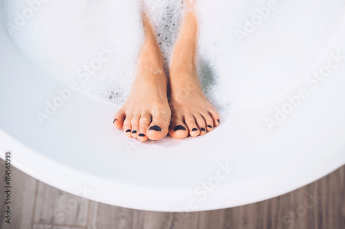 Photo  Well groomed woman's legs in bath foam close up image