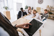 close-up shot of businesswoman using tablet with blurred colleagues sitting on background