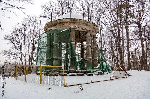 Repair work at an abandoned stone rotunda in a winter park Wallpaper Mural