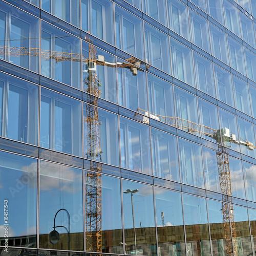 Spiegelung eines Baukranes in der Glasfassade eines Bürogebäudes in Berlin Poster