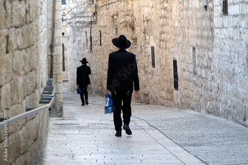 Naklejka premium Dwóch nierozpoznanych religijnych Żydów idących ulicą Starego Miasta w Jerozolimie.