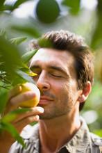 Man Smelling At Orange