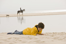 Young Boy Lying On Sand At Beach
