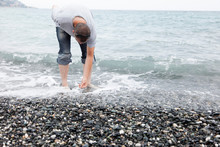 Man Collecting Pebbles On Rock...