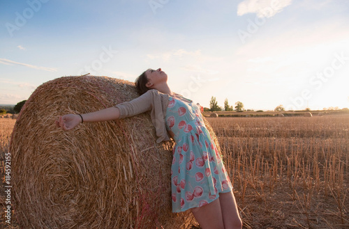 Photo Girl leaning on haystack in field