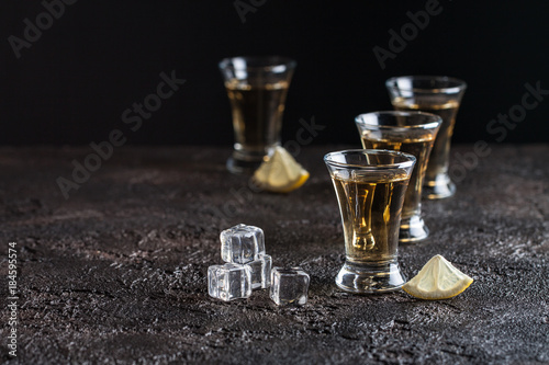 Foto op Plexiglas Bar Strong whiskey in glasses with ice and sliced lemon on the dark background