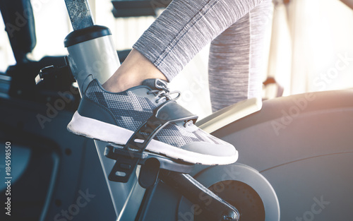 Photo  Woman feet is cycling on fitness spinning bike machine
