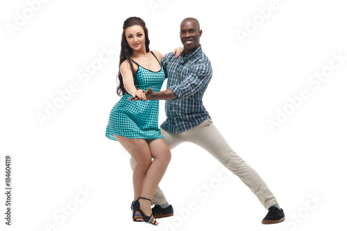 Fotografie, Obraz  Black man and caucasian woman in casual clothes in incendiary dance isolated on white background