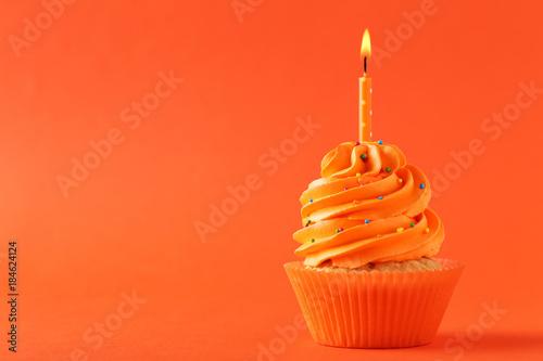 Photo  Tasty cupcake with candle on orange background