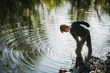 Boy Standing In A Lake Looking...