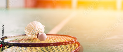 Photo Badminton ball (shuttlecock) and racket on court floor