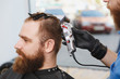 Close up of male professional hairdresser serving client by clipper. Ginger handsome stylish young man with big beard and short hair getting trendy haircut in black cape. Light white barber shop room.