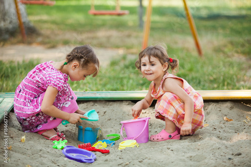 Obraz na plátně Two girls play in the sandbox