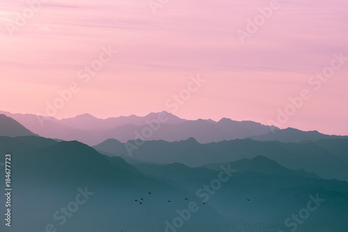 Spoed Foto op Canvas Groen blauw Mountain range at sunrise light