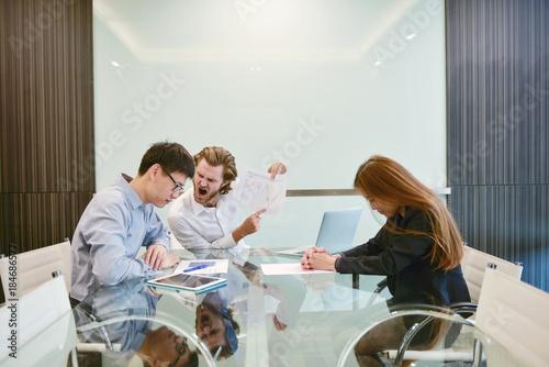 Carta da parati Blonde business man blaming Asian employee in meeting room