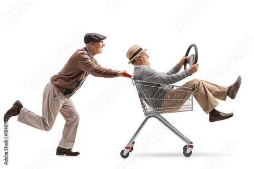 Fotografía Senior pushing a shopping cart with another senior with a steering wheel riding