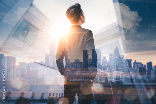 Obraz na plátně The double exposure image of the business man standing back during sunrise overlay with cityscape image