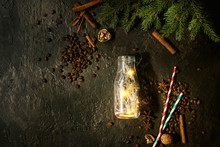 Christmas Lights Garland In Glass Bottle With Coffee Beans, Spices, Nuts, Cocktail Tube, Fir Tree Branches In Wooden Tray Over Dark Texture Background. Christmas Holiday Mood Card. Top View, Space