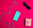 canvas print picture - Women's accessories are lined on a red background. Smartphone, headphones, wallet, sunglasses. Flat lay.
