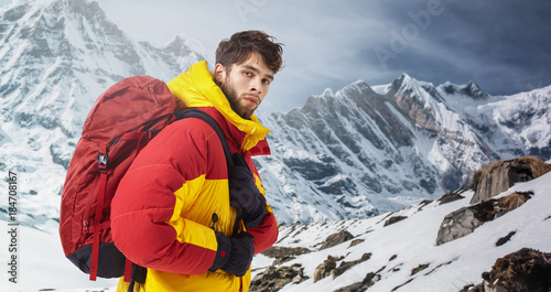 Poster de jardin Alpinisme Mountaineer in winter clothes with hiking equipment against snowy landscape