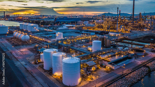 Aerial view oil terminal is industrial facility at night for storage of oil and petrochemical products ready for transport to further storage facilities in city skyline Fototapet