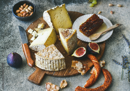 Keuken foto achterwand Cheese platter with cheese assortment, figs, honey, freshly baked bread and nuts on wooden board over grey concrete background. Party or gathering eating concept