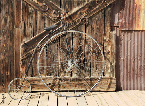 Printed kitchen splashbacks Bicycle Old High Wheel Bicycle in Front of Whethered Barn Door