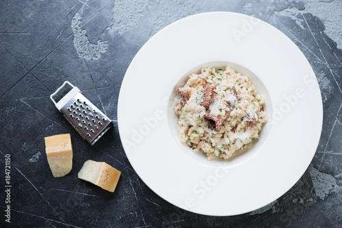 Risotto with chanterelle mushrooms and parmesan served in a white plate. View from above on a grey stone background