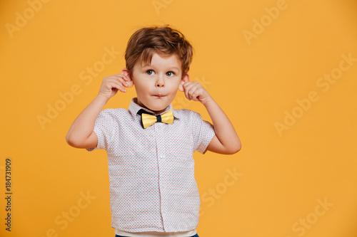 Funny little boy child standing isolated over yellow Tapéta, Fotótapéta