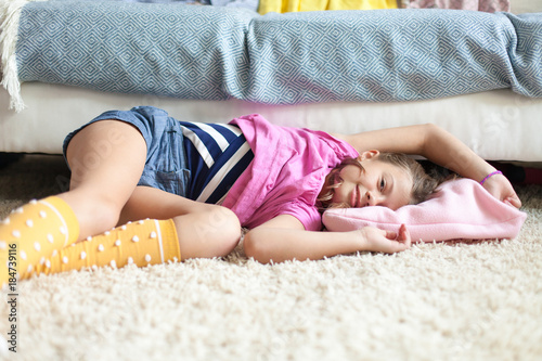 Content preteen girl laying on the floor in the living room, looking at camera