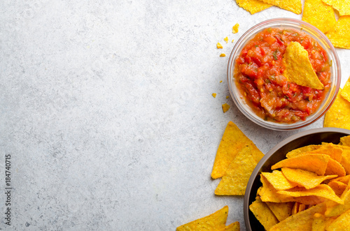Leinwand Poster Traditional mexican homemade salsa sauce in a glass bowl and a b