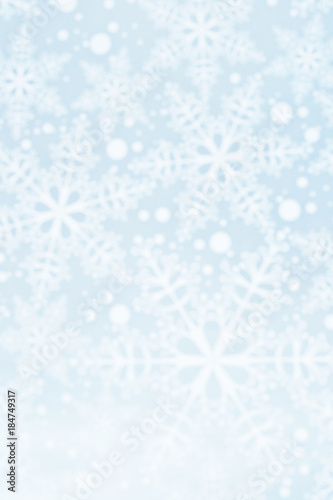 Light defocused winter background with blue snowflakes, vertical image