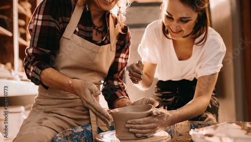 Two women at a pottery workshop making clay pots Fototapeta