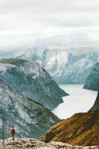 Man backpacker hiking in Norway mountains landscape Travel Lifestyle concept active vacations outdoor exploring nature of Scandinavia aerial view