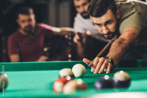 Foto young handsome man playing in pool with friends at bar