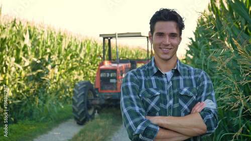 Fototapeta Portrait of a beautiful young farmer (student) working in the field with a tractor working in a tablet, happy, in a shirt, corn field. Concept ecology, transport, farmers, clean air, food, bio product obraz