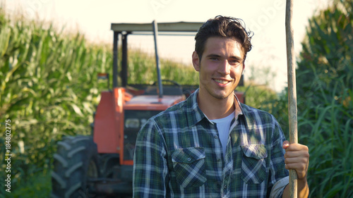 Leinwand Poster Portrait of a beautiful young farmer (student) working in the field with a tractor working in a tablet, happy, in a shirt, corn field