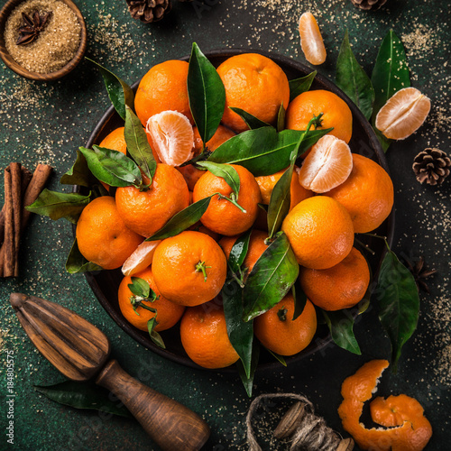 fresh clementines (tangerines) with spices on dark greeen background, top view. Winter or Christmas food concept