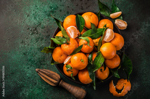 fresh clementines (tangerines) with leaves on dark greeen background