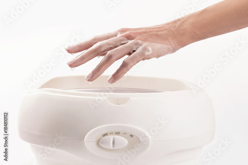 Fotografie, Tablou Woman in a nail salon receiving a manicure, she is bathing her hands in paraffin
