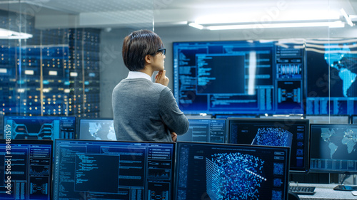 In the System Control Room Technical Operator Stands and Monitors Various Activities Showing on Multiple Displays with Graphics. Administrator Monitors Work of Artificial Intelligence.