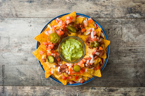 Fotomural Mexican nachos with beef, guacamole, cheese sauce, peppers, tomato and onion in plate on wooden table