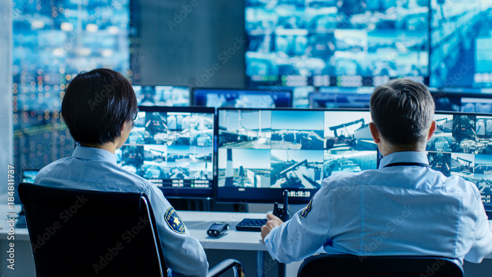Fototapety, obrazy: In the Security Control Room Two Officers Monitoring Multiple Screens for Suspicious Activities, They Report any Unauthorised Activities. They Guard Object of National Importance.