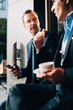 Businessman looking at male colleague talking while holding coffee cup at cafe