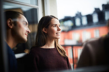 Smiling Woman With Friends Looking Away While Standing In Balcony Of Rental Apartment