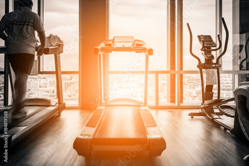 Obraz na plátně Fitness hall with people running on treadmill next to window with daylight morni